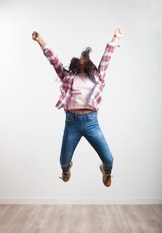 A menina que salta com os braços estendidos