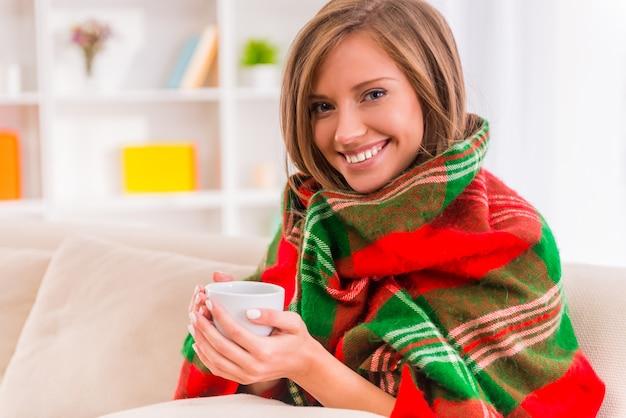 A menina que senta-se em casa envolveu em um cobertor e guarda o café.