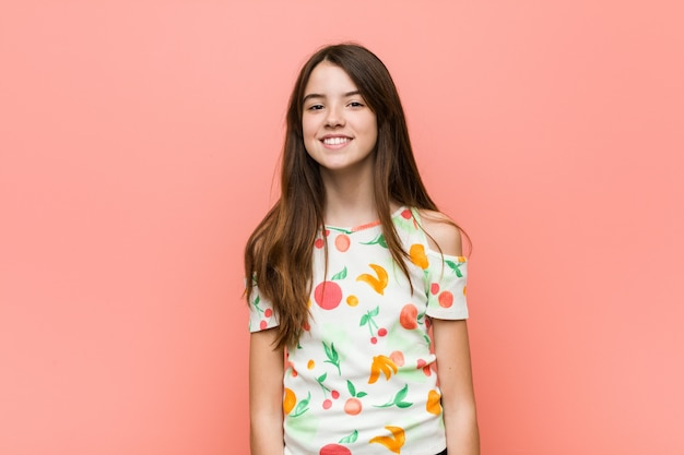 A menina que veste um verão veste-se contra uma parede feliz, sorridente e alegre.