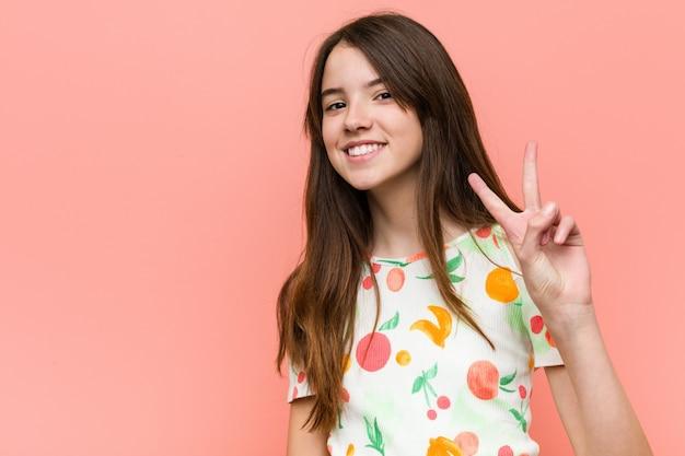 A menina que veste um verão veste-se contra uma parede vermelha que mostra o sinal da vitória e que sorri amplamente.