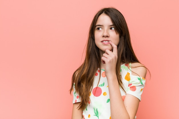 A menina que veste um verão veste-se contra uma parede vermelha que olha lateralmente com expressão duvidosa e cética.