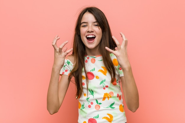 A menina que veste um verão veste-se contra uma virada vermelha da parede que grita com mãos tensas.