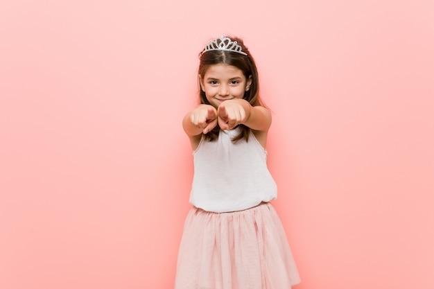 A menina que veste uma princesa olha sorrisos alegres que apontam para a frente.