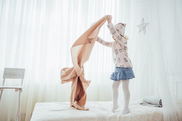 A menina quer enrolar um cobertor na luz do quarto