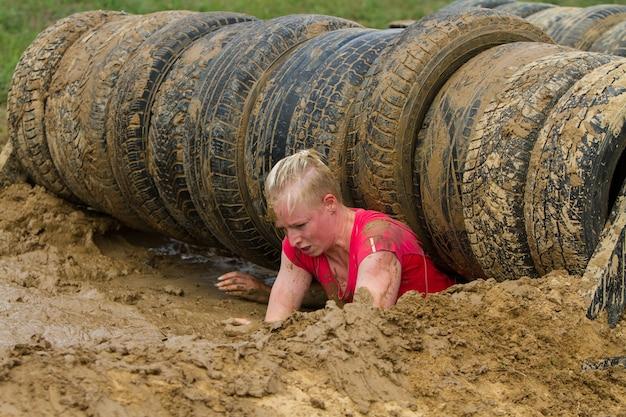A menina rasteja na lama, superando emocionalmente o obstáculo feito de pneus.