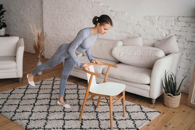 A menina realiza exercícios para as nádegas em casa fazendo esportes em casa online estilo de vida saudável exercício com uma cadeira para fortalecer os músculos