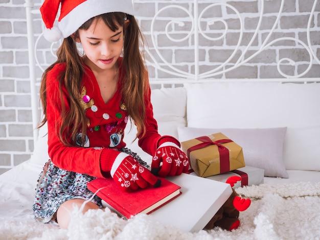 A menina recebeu o livro vermelho como presente no dia de natal