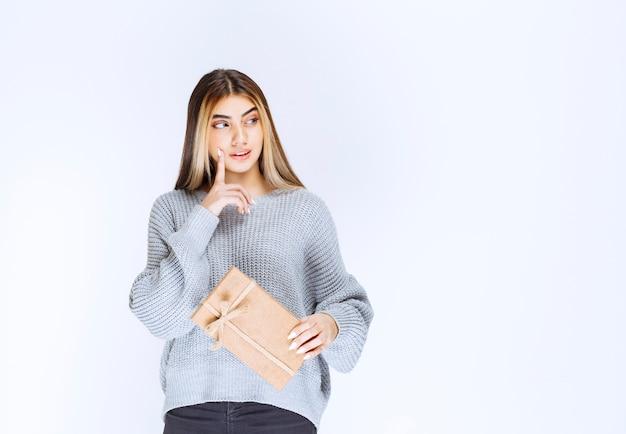 A menina recebeu uma caixa de papelão de um remetente desconhecido e pensativo.