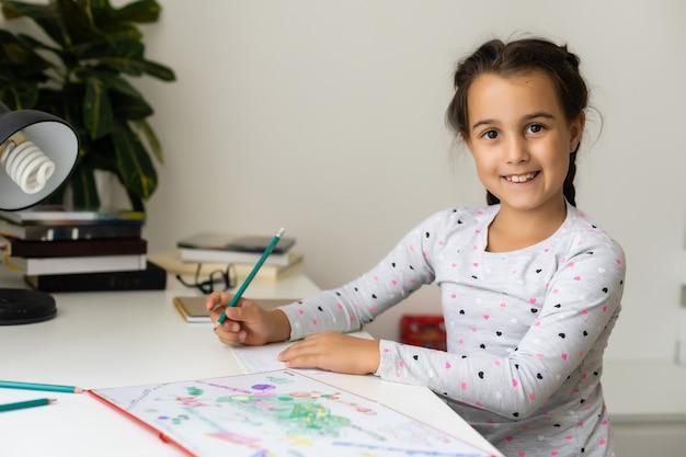 A menina rindo, pintando lápis coloridos em sua mesa de jogo
