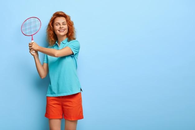 A menina ruiva ativa segura uma raquete de tênis, vestida com uma camiseta azul casual e shorts vermelhos, gosta de jogar com um amigo e tem uma expressão feliz