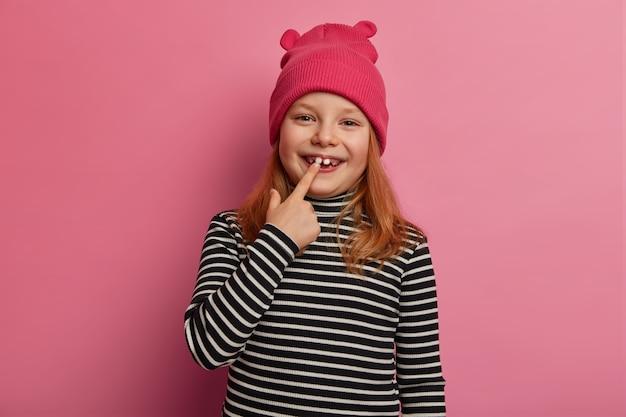 A menina ruiva bonita mostra seus primeiros dois dentes adultos, ri e se alegra, expressa emoções positivas, mantém a boca aberta, se prepara para o check-up oral, vestida com um suéter listrado e chapéu rosa