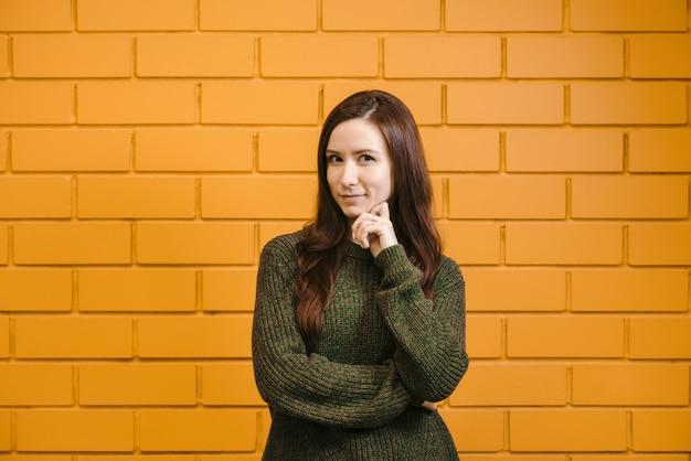 A menina ruiva bonita que veste vidros e uma camisola verde está sorrindo contra um fundo amarelo da parede de tijolo.
