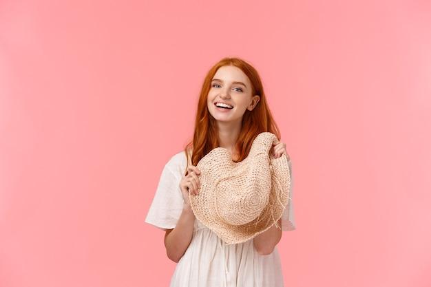 A menina ruiva macia, carismática e atraente, balançada na cintura, arrumada para as férias de verão, pronta para viajar para o exterior, segurando um chapéu de palha, rindo e sorrindo a câmera. fundo rosa de pé