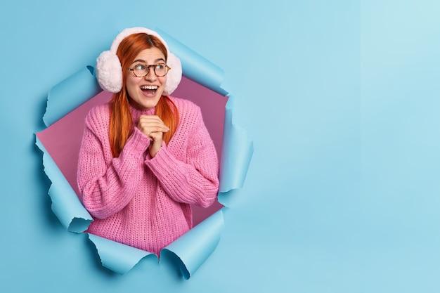 A menina ruiva muito alegre mantém as mãos juntas e olha com uma expressão feliz e impressionada vestida com um suéter de inverno quente e protetores de ouvido
