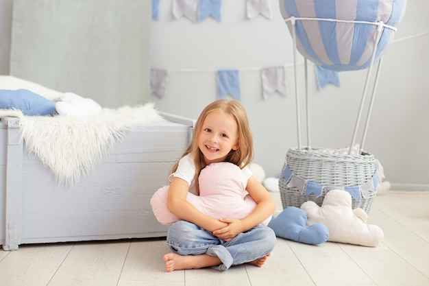 A menina ruiva senta-se no assoalho que abraça o travesseiro da nuvem contra o balão decorativo.