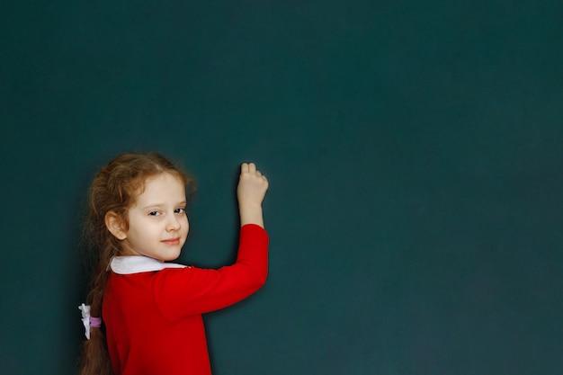 A menina ruivo encaracolado escreve no giz está perto da administração da escola.