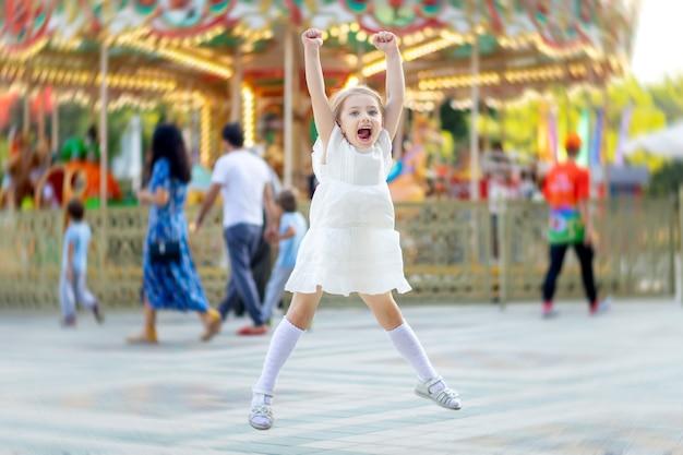 A menina salta e sorri de felicidade em um parque de diversões no verão