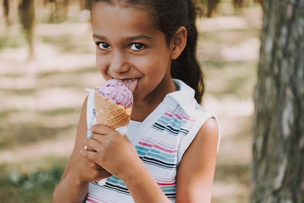 A menina satisfeita nova come o gelado na floresta.