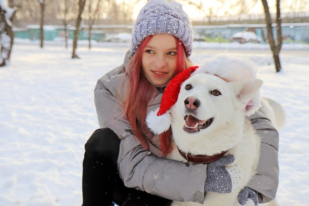 A menina se comunica alegremente com o cachorro de chapéu de papai noel na natureza no inverno.
