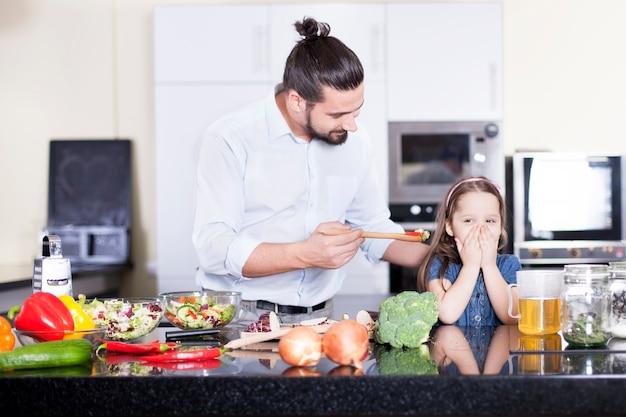 A menina se recusa a comer salada enquanto cozinha com o pai na cozinha