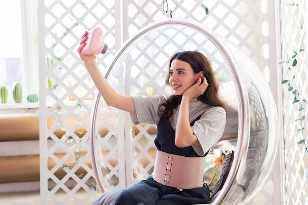 A menina se senta em uma cadeira transparente e tira uma foto da selfie na câmera instantânea