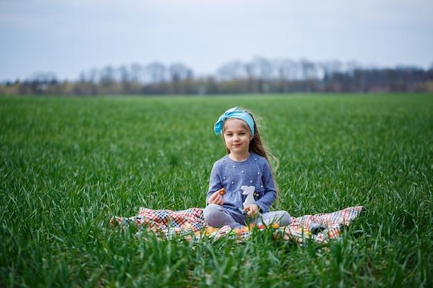 A menina se senta na colcha e come biscoitos e geleia, grama verde no campo, clima ensolarado de primavera, sorriso e alegria da criança, céu azul com nuvens