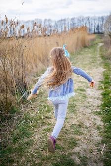 A menina segura juncos secos nas mãos e corre ao longo de uma trilha na floresta, clima ensolarado de primavera, sorrindo e a alegria da criança