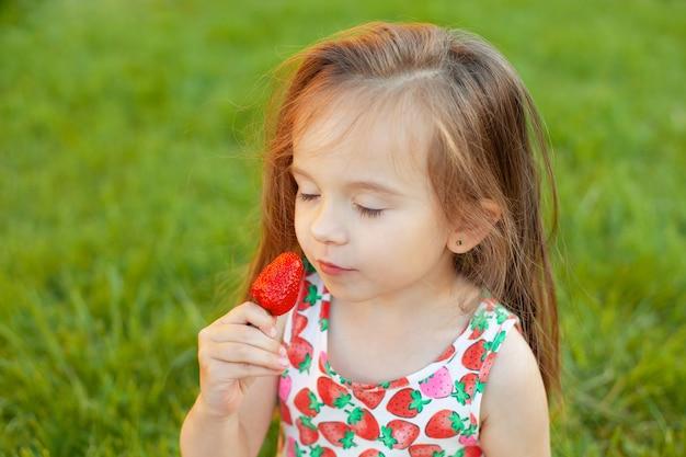 A menina segura morangos na mão e cheira seu aroma. felicidade de verão