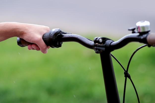 A menina segura o guidão da bicicleta