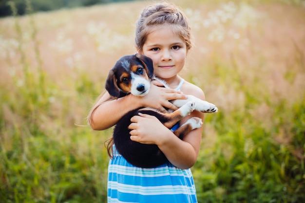 A menina segura um filhote de cachorro em seus braços