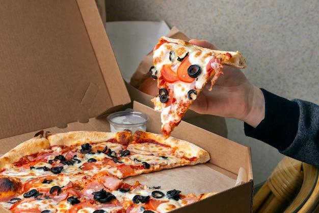 A menina segura um pedaço de pizza na mão. entrega de comida não saudável de fast food