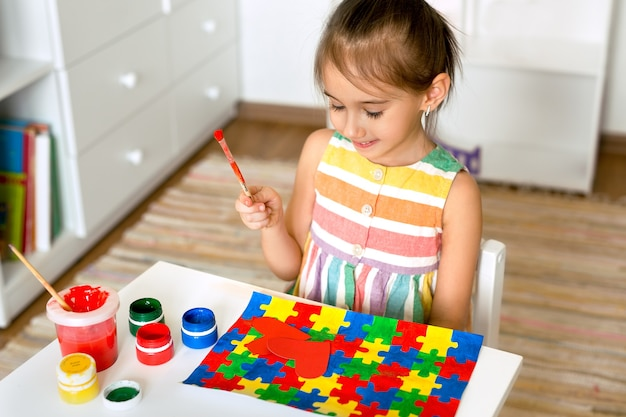 A menina segura um pincel nas mãos e olha seu desenho para o dia do autismo