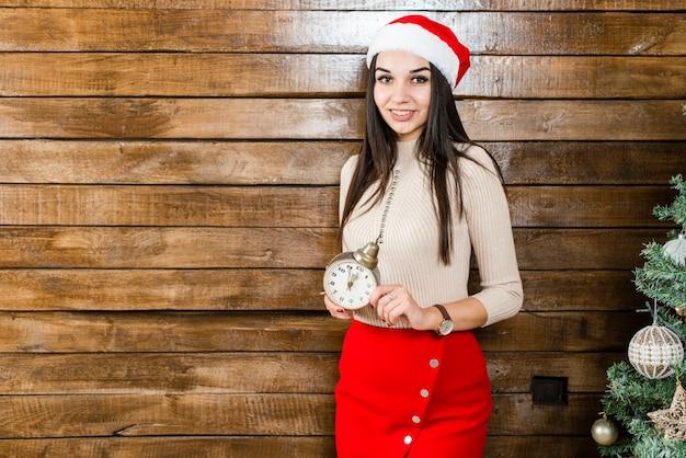 A menina segura um relógio na sala de natal decorada