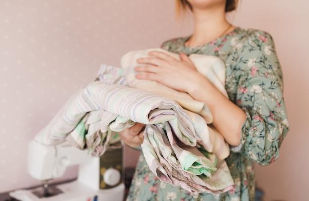 A menina segura uma pilha de roupas de cama coloridas nas mãos