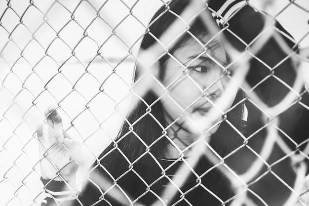 A menina segurando a jaula, preso, retardado, abuso infantil em tom branco