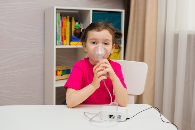 A menina senta e inala através de um nebulizador na sala