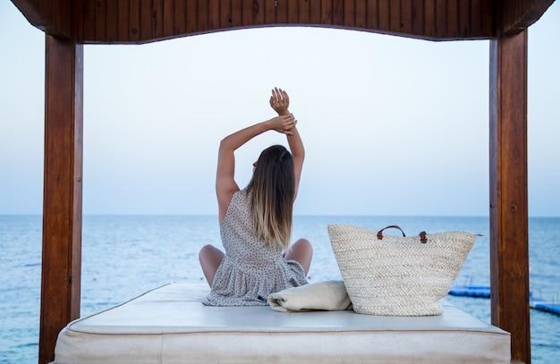 A menina senta-se à beira-mar e relaxa