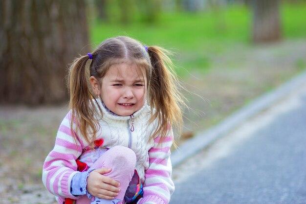 A menina senta-se na estrada e chora, segurando um joelho
