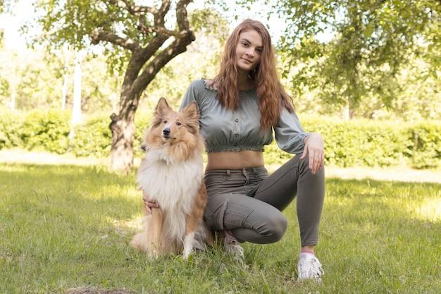 A menina senta-se na grama com seu cão amado