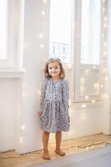 A menina senta-se perto da janela decorada com uma guirlanda para o feriado, a sala é decorada para o natal