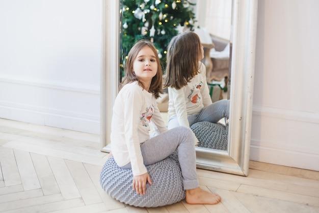 A menina senta-se perto do espelho, o espelho reflete a árvore de natal e as luzes