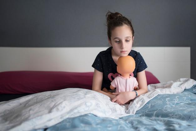 A menina sentada na cama parece triste, apoiando o queixo no pulso.