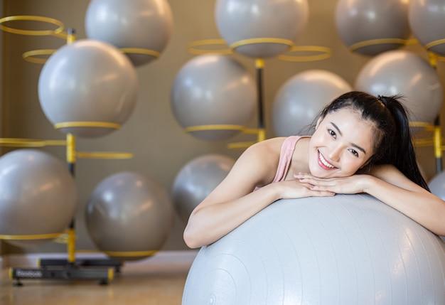 A menina sentada relaxa com a bola no ginásio.