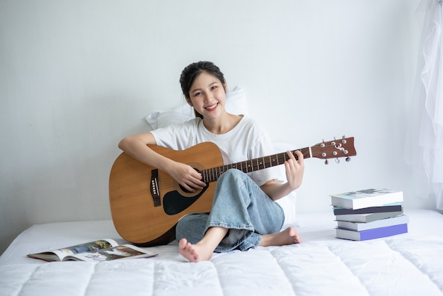 A menina sentou-se e tocou violão na cama.