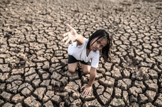 A menina sentou-se em outro lugar, mão no céu para pedir chuva no chão seco, aquecimento global
