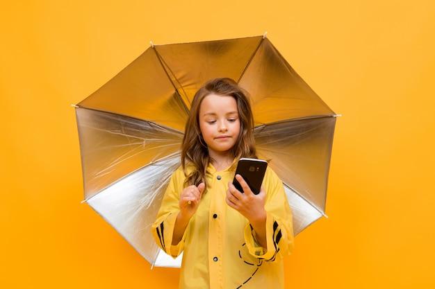 A menina sob um guarda-chuva aberto senta-se no telefone em um fundo amarelo