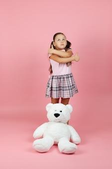 A menina sonhadora e pensativa faz sinal de positivo com um ursinho de pelúcia branco perto de seus pés