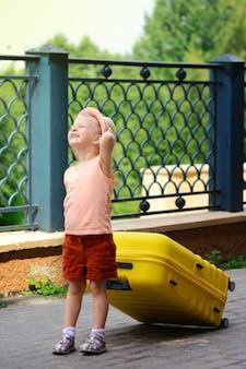 A menina sorri e faz uma careta ao sol. uma criança de chapéu e bermuda vermelha está carregando uma grande mala amarela.