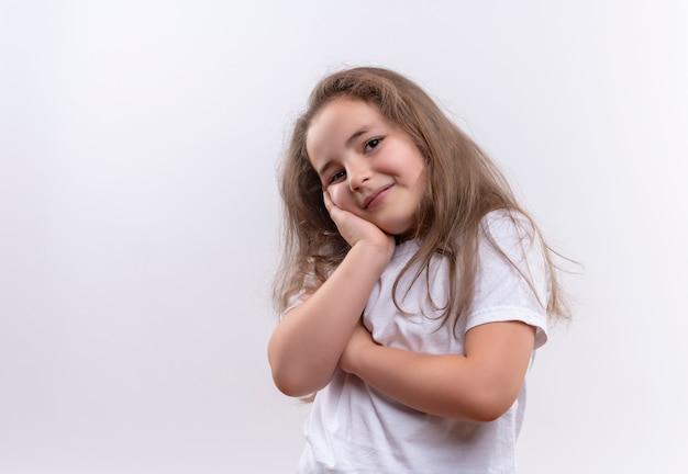 A menina sorridente da escola vestindo uma camiseta branca colocou a mão na bochecha em um fundo branco isolado