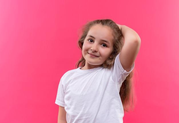 A menina sorridente da escola vestindo uma camiseta branca colocou a mão na cabeça em um fundo rosa isolado